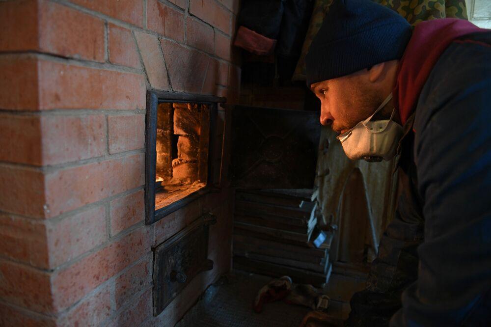Kominiarz Maksim pali w oczyszczonym piecu podczas pracy w rejonie siergijew-posadzkim obwodu moskiewskiego.