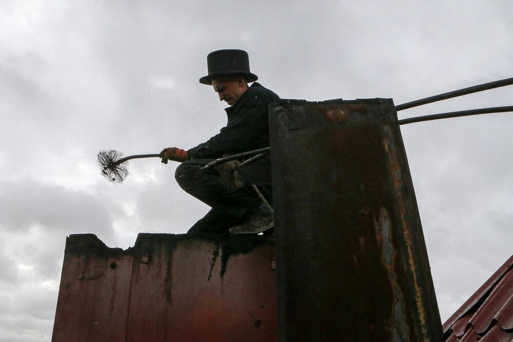Pracownik firmy Truboczyst, kominiarz Maksim Czerkesow czyści przewody w Kaliningradzie.
