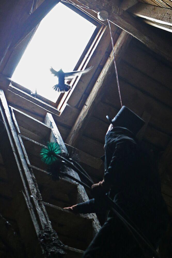 Pracownik firmy Truboczyst, kominiarz Maksim Czerkesow, wchodzi na dach domu w Kaliningradzie.