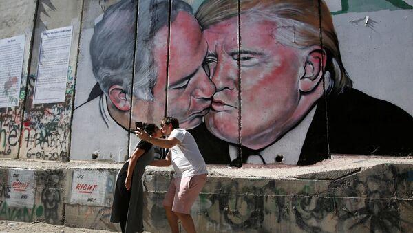 Turyści całujący się na tle graffit przedstawiającego pocałunek Trumpa i Netanjahu - Sputnik Polska