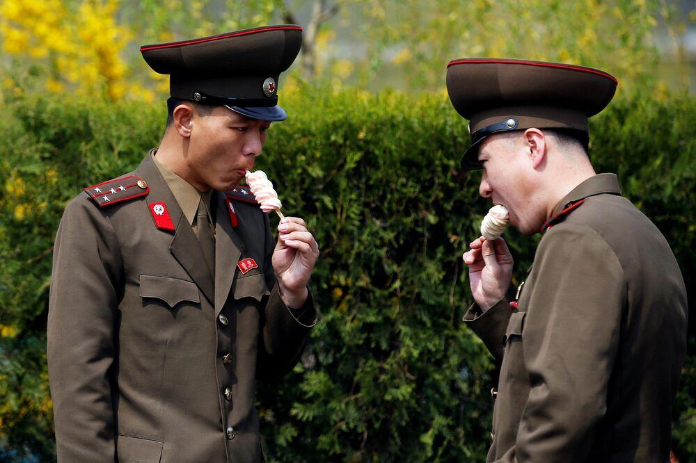 Wojskowi jedzą lody w Pjongjangu.