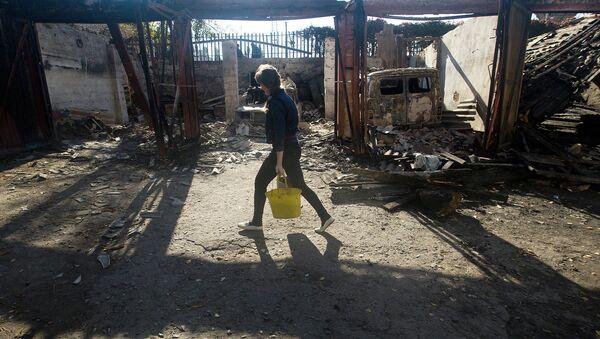 Kobieta niesie wodę we wsi pod Ługańskiem - Sputnik Polska