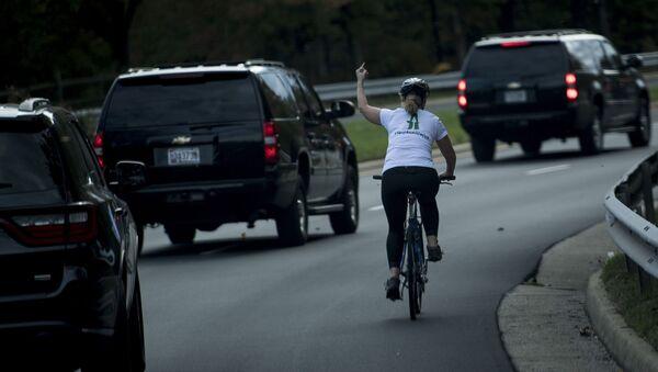 Rowerzystka pokazuje środkowy palec kolumnie prezydenta USA Donalda Trumpa - Sputnik Polska