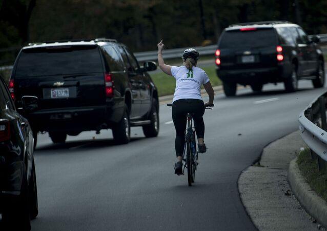 Rowerzystka pokazuje środkowy palec kolumnie prezydenta USA Donalda Trumpa
