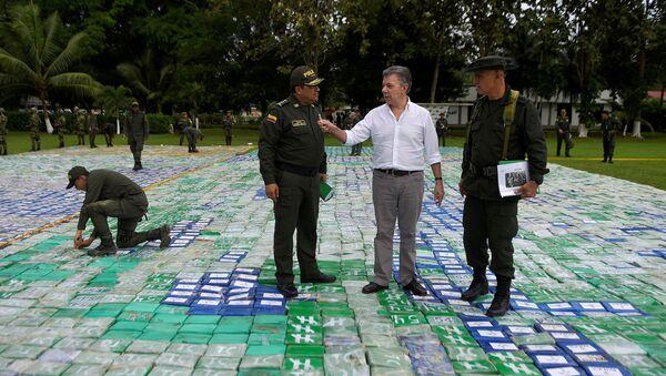 Prezydent Kolumbii Juan Manuel Santon na improwizowanym polu z cegiełek z kokainą w otoczeniu funkcjonariuszy służb specjalnych - Sputnik Polska