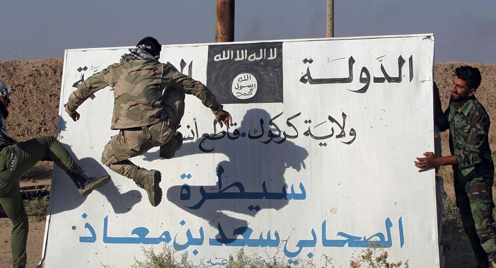 Iraccy wojskowi niszczą tablicę z flagą Daesh, Irak