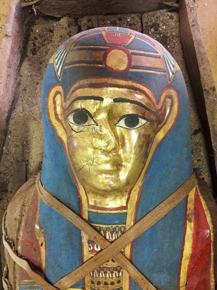 Głowa mumii jest zakryta maską ze sprasowanego papirusa, pozłacaną i pomalowaną niebieską farbą. Wyobrażony jest na niej bóg nieba Khebr.