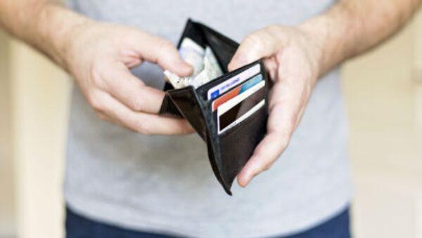 Человек держит кошелёк с деньгами - Sputnik Polska