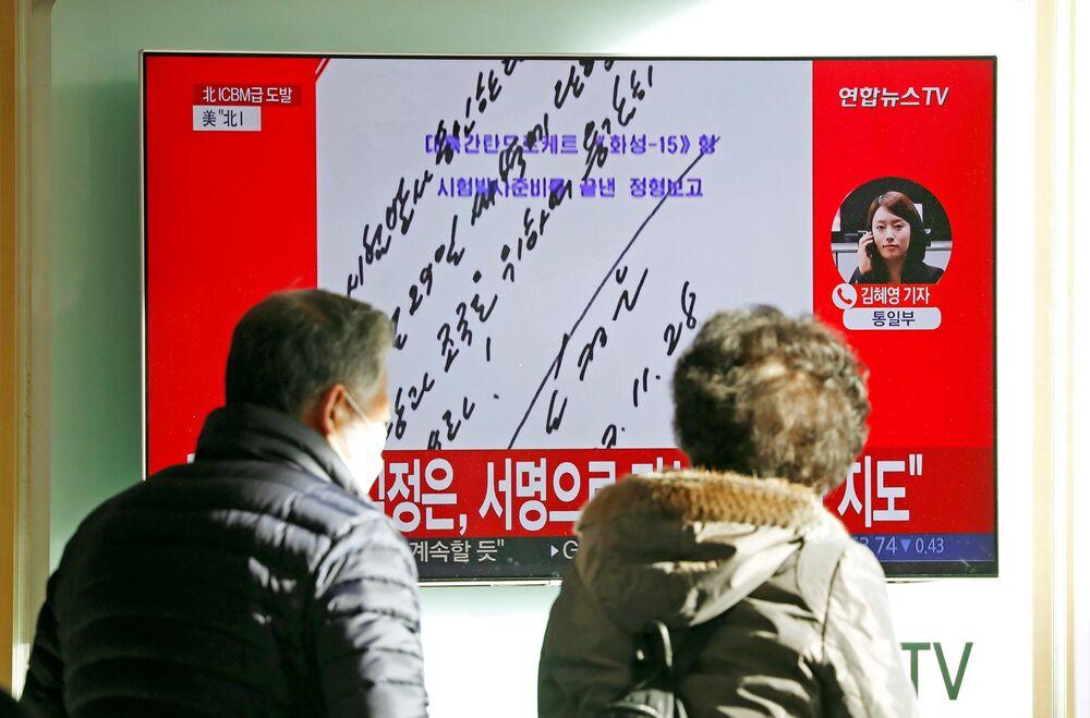 Ludzie oglądają wiadomości w telewizji o wystrzale międzykontynentalnej rakiety balistycznej Hwasong-15 w Seulu