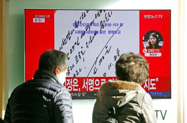 Ludzie oglądają wiadomości w telewizji o wystrzale międzykontynentalnej rakiety balistycznej Hwasong-15 w Seulu - Sputnik Polska