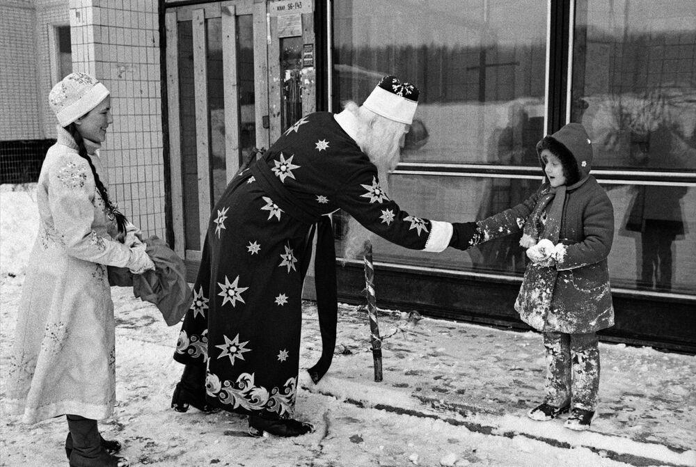 Święty Mikołaj składa życzenia dziewczynce z okazji Nowego Roku na ulicy, 1985 rok