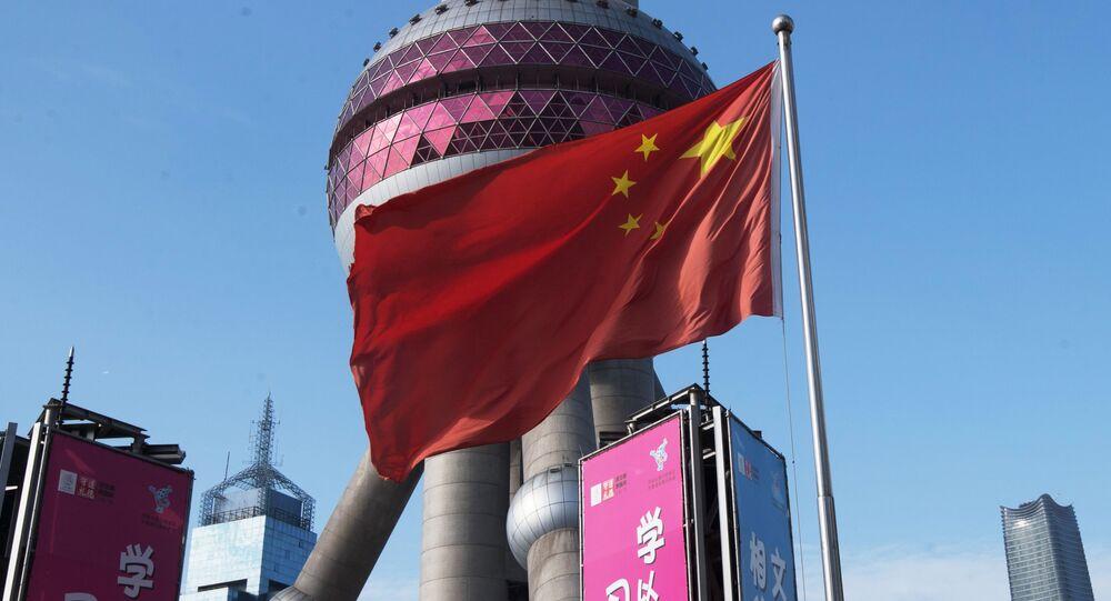 Flaga Chińskiej Republiki Ludowej na tle wieży telewizyjnej Oriental Pearl w dzielnicy Pudong w Szanghaju