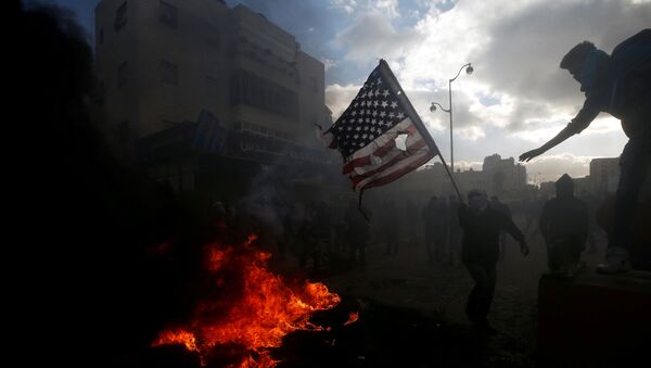Palestyńczycy palą amerykańską flagę podczas starć z izraelską policją w związku z protestami przeciwko decyzji Donalda Trumpa o uznaniu Jerozolimy za stolicę Izraela - Sputnik Polska