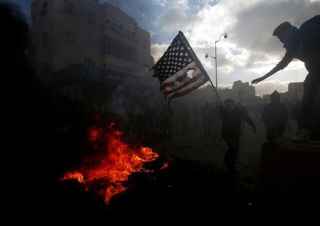 Palestyńczycy palą amerykańską flagę podczas starć z izraelską policją w związku z protestami przeciwko decyzji Donalda Trumpa o uznaniu Jerozolimy za stolicę Izraela
