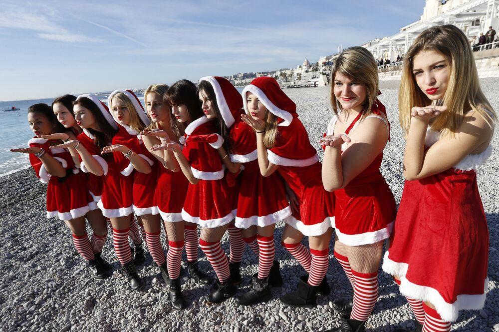 Dziewczyny w kostiumach Świętego Mikołaja na plaży w Nicei, Francja