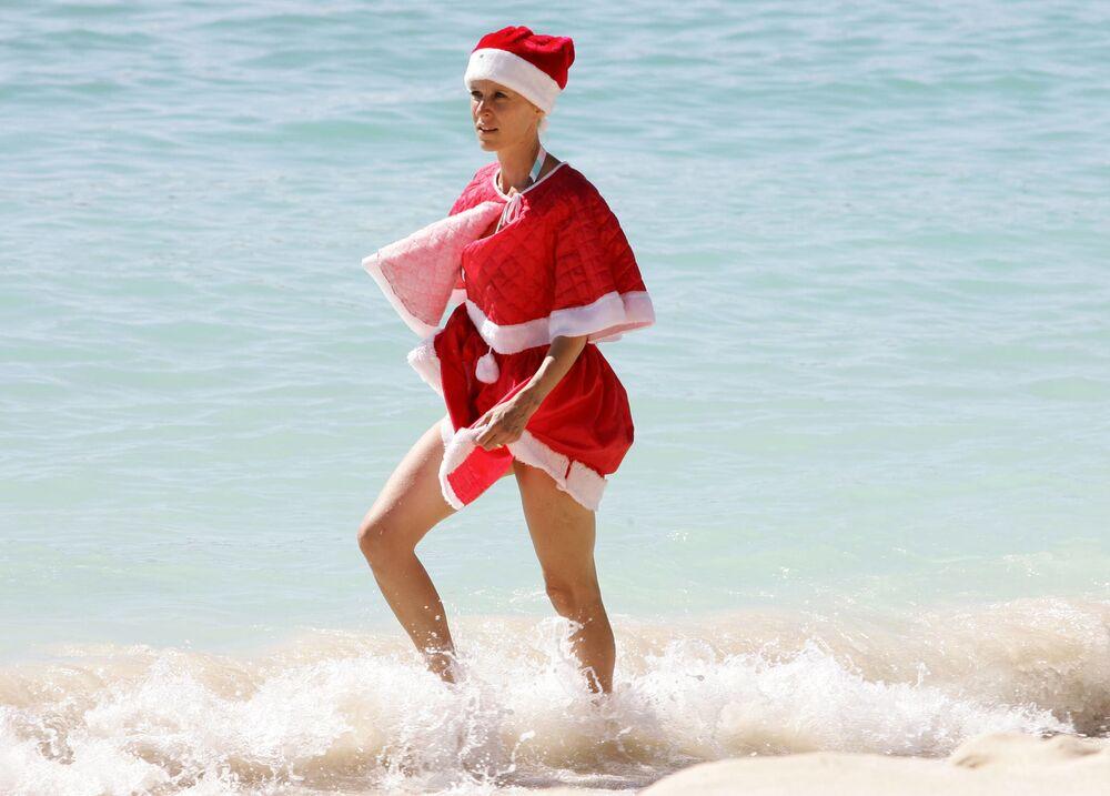 Kobieta w kostiumie Świętego Mikołaja na plaży w Gwadelupie, Francja