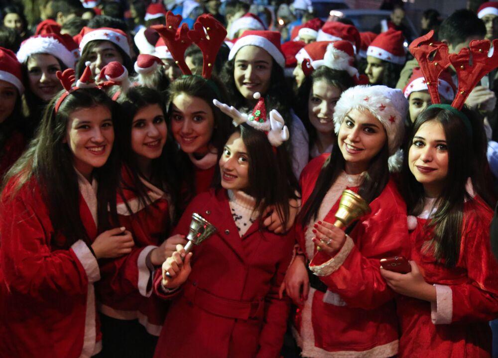Syryjskie dziewczyny w kostiumach Świętego Mikołaja