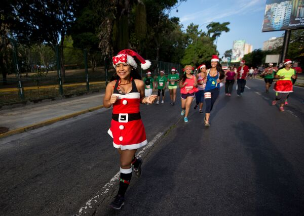 Uczestnicy wyścigów ubrani w kostiumy Świętego Mikołaja w Wenezueli - Sputnik Polska