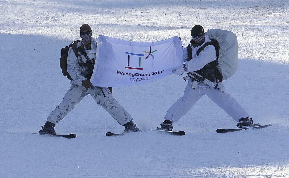 Żołnierze piechoty morskiej z USA i Korei Południowej trzymaja flagę Zimowych Igrzysk Olimpijskich 2018 w Pjongczangu.