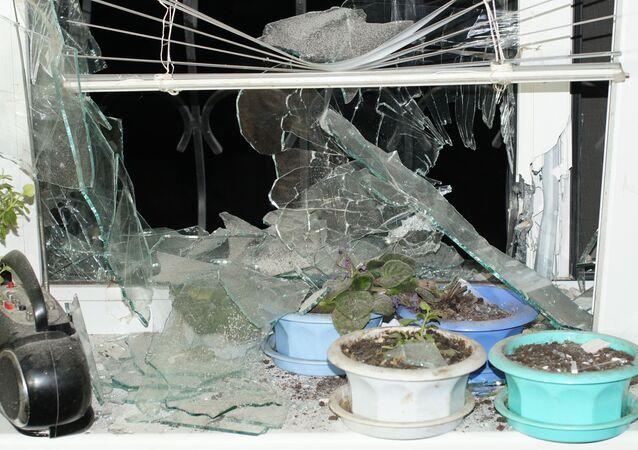 Okno ostrzelanego domu w miejscowości Stachanow w obwodzie ługańskim