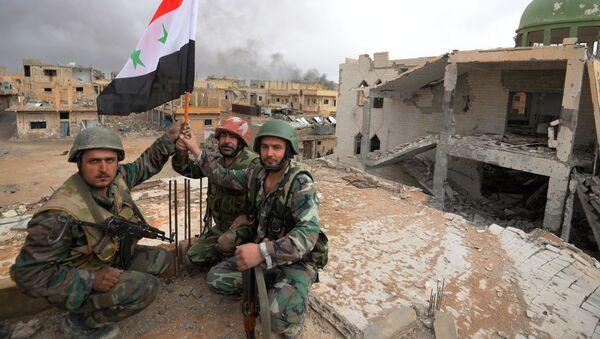 Żołnierze z flagą Syrii w Palmyrze - Sputnik Polska
