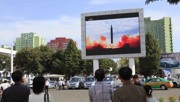 Przechodnie w Pjongjangu oglądają wiadomości o wystrzeleniu rakiety balistycznej Hwasong-12 - Sputnik Polska