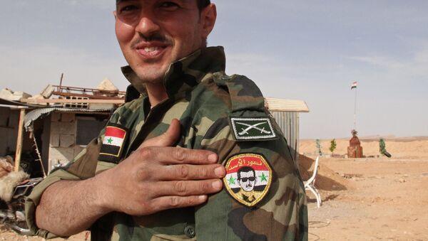 Żołnierz Syryjskiej armii demonstruje naszywkę z portretem Baszara Asada na syryjsko-libańskiej granicy - Sputnik Polska