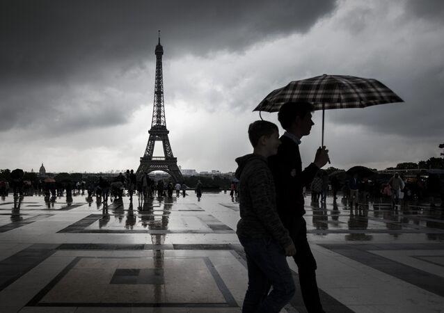 Turyści spacerujące pod parasolem niedaleko wieży Eiffla