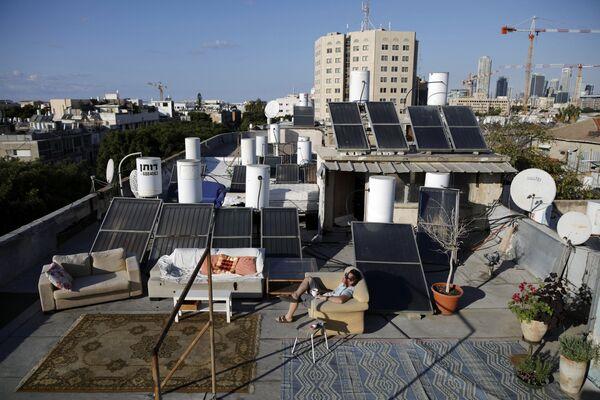 Mężczyzna siedzi na kanapie na dachu budynku w Tel Awiwie. - Sputnik Polska