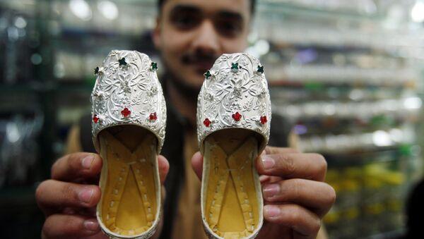 Sprzedawca pokazuje srebrne pantofelki w sklepie jubilerskim na bazarze w Peszewarze, Pakistan. - Sputnik Polska