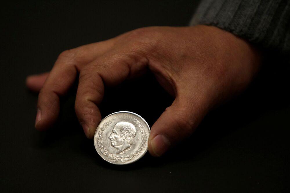 Mężczyzna pokazuje meksykańską srebrną monetę Idalgo 5 peso w kantorze w Ciudad Juárez, Meksyk.