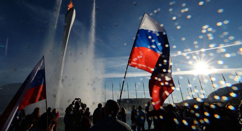 Kibice przy pojemniku z ogniem olimpijskim w Soczi