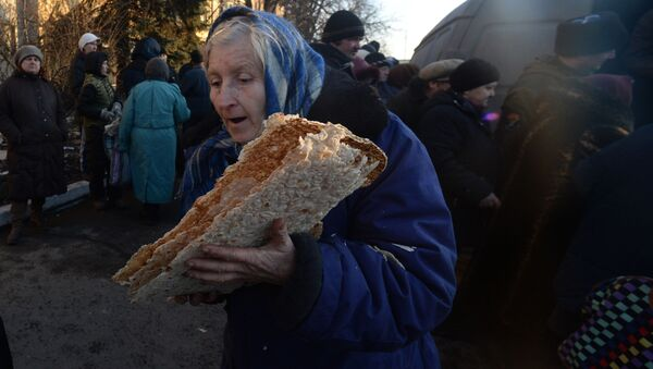 Starsza kobieta w czasie rozdawnictwa pomocy humanitarnej dla mieszkańców Debalcewa - Sputnik Polska