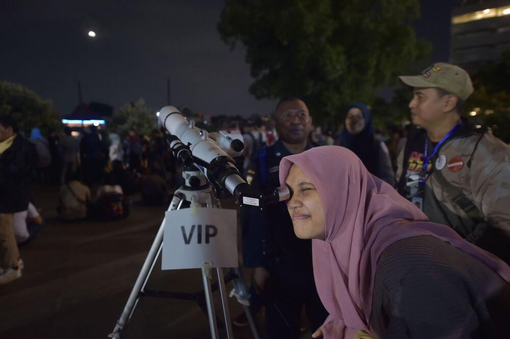 Kobieta obserwuje zaćmienie Superksiężyca w Indonezji
