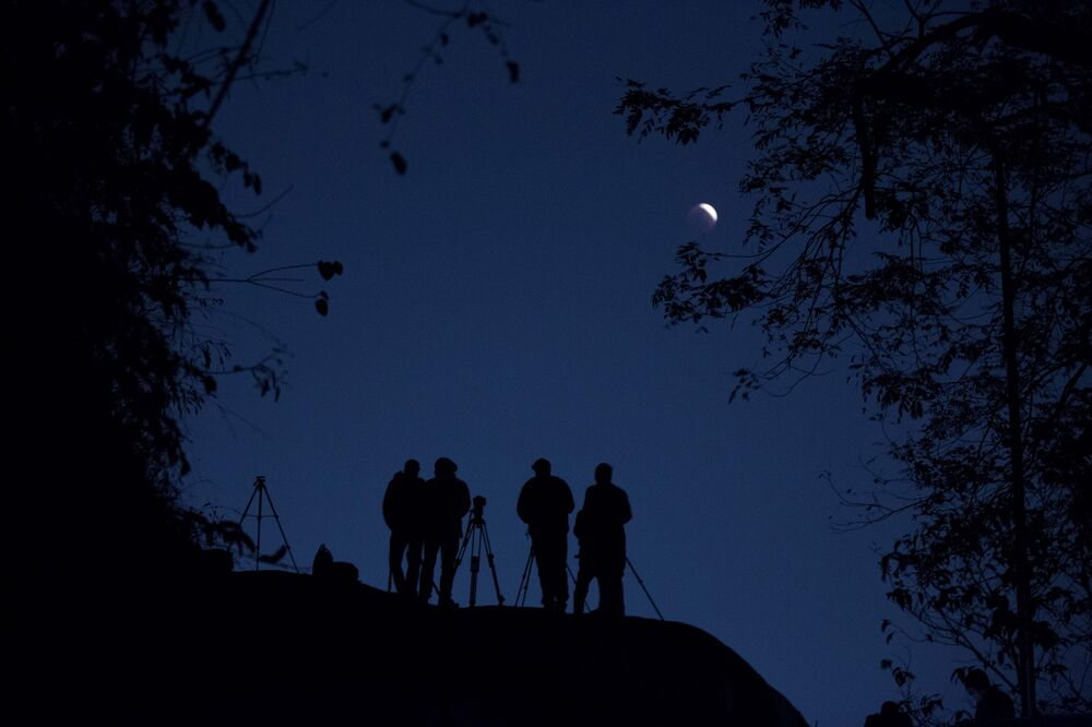 Ludzie obserwują zaćmienie Księżyca w Gauhati, Indie