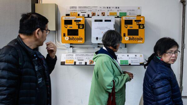 Pedestrians walk past ATM machines (L and R) for digital currency Bitcoin in Hong Kong on December 18, 2017 - Sputnik Polska