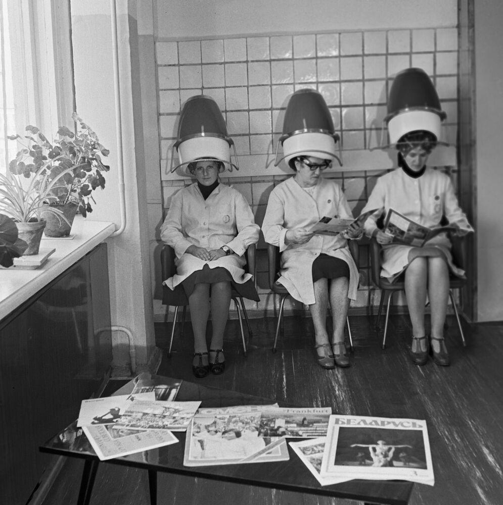 Pracownice fabryki lnu siedzą w salonie fryzjerskim pod suszarkami do włosów, 1980 rok.