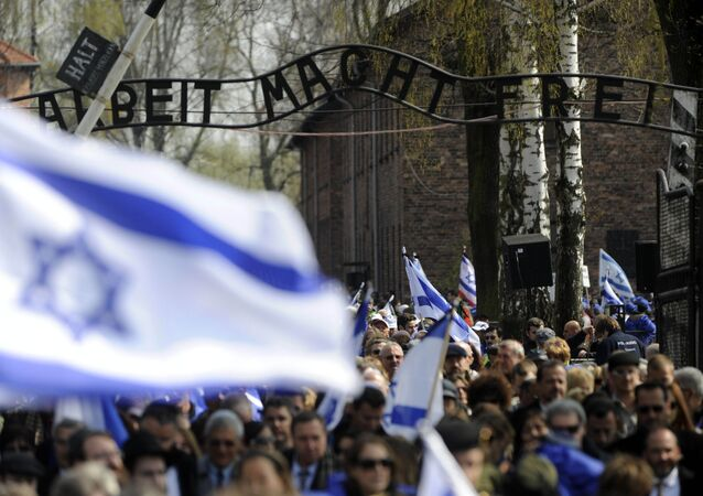 Participants of the annual March of Living walk under the main entrance with the inscription 'Arbeit Macht Frei', in Auschwitz (Oswiecim) , Poland