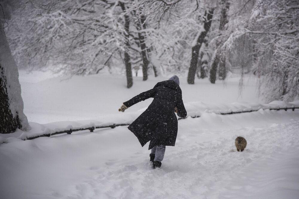 Kobieta spaceruje z psem podczas opadów śniegu w Ogrodzie Botanicznym w Moskwie