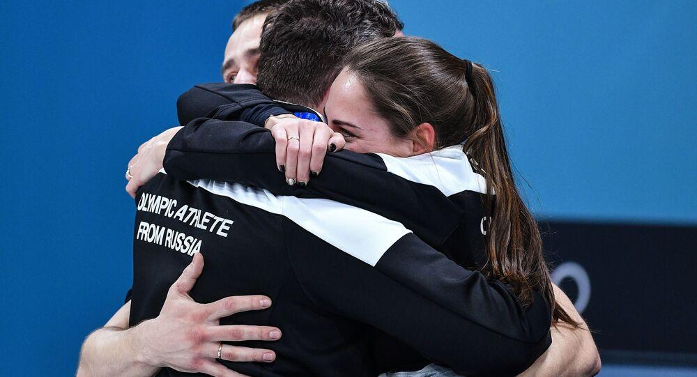 Rosyjscy sportowcy Anastasija Bryzgałowa, Aleksander Kruszelnicki i ich trener Wasilij Gudin cieszą się ze zwycięstwa w meczu o trzecie miejsce turnieju w curlingu Rosja-Norwegia na XXIII Zimowych Igrzyskach Olimpijskich