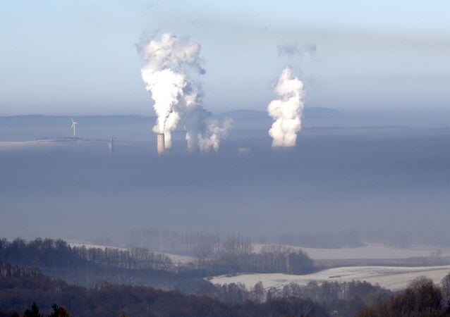 Dymiące kominy elektrowni węglowej w polskiej miejscowości Bogatynia, widoczne ze strony Czech