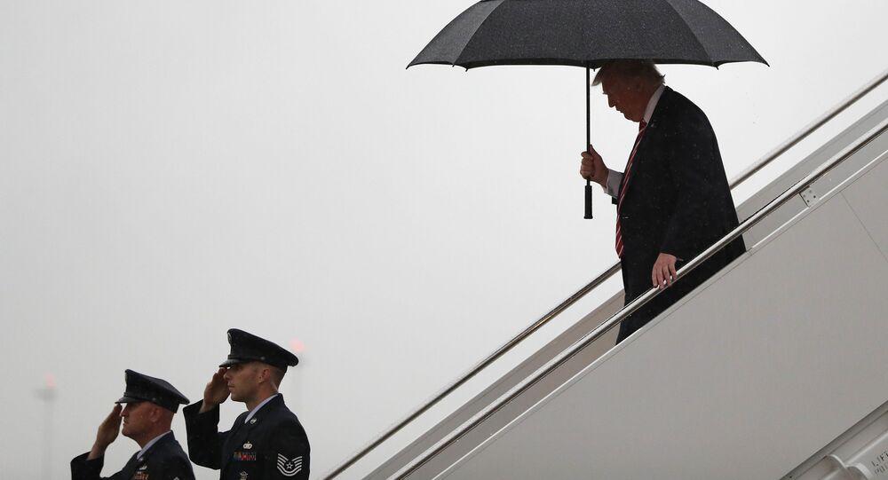 Prezydent USA Donald Trump pod parasolem na lotnisku