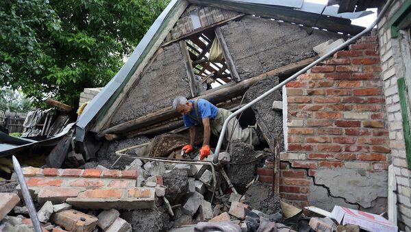 Ratownik stara się odnaleźć kobietę po gruzami domu niedaleko Gorłowki - Sputnik Polska