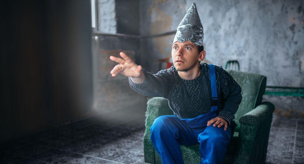 Mężczyzna w foliowej czapce przed telewizorem