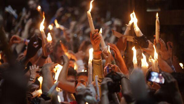 Wierzący ze świeczkami w czasie zstąpienia Świętego Ognia w Bazylice Grobu Świętego w Jerozolimie - Sputnik Polska