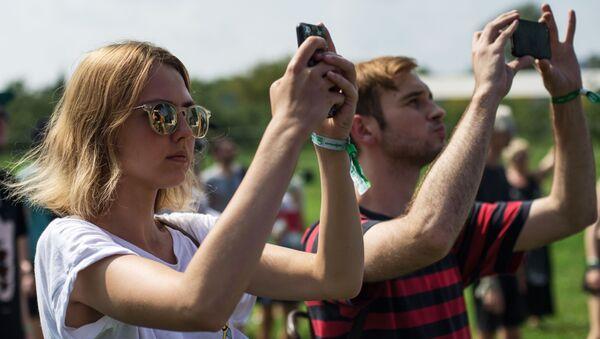 Uczestnicy festiwalu Piknik. Afiszy w Moskwie z telefonami - Sputnik Polska