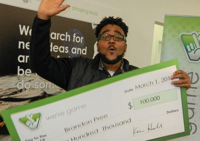 Brandon Pree z czekiem o wartości 100 tysięcy dolarów po wygranej na loterii Virginia Lottery