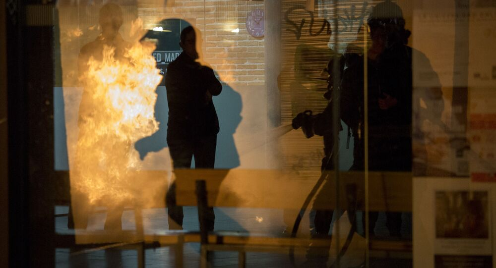 Strażacy próbują ugasić pożar podczas protestu po śmierci ulicznego sprzedawcy w Madrycie