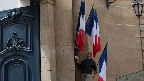 Mężczyzna ustawia flagi Francji na ścianie oficjalnej rezydencji premiera Francji Hotel de Matingnon w Paryżu - Sputnik Polska