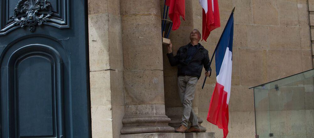 Mężczyzna ustawia flagi Francji na ścianie oficjalnej rezydencji premiera Francji Hotel de Matingnon w Paryżu